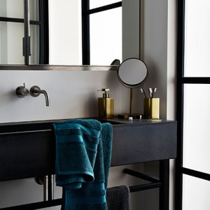 Dark poetry prevails in this beautiful bathroom with black details (faucet, sink, mirror frame). The brass accessories compliment the dark setting in the most elegant way. Image by Argos.