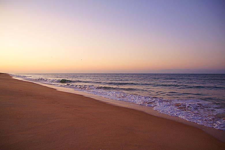 A sandy beach shoreline with a pinkish sky.