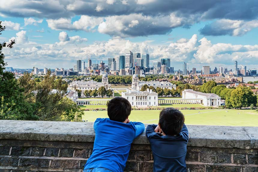Two boys looking at the view of the Greenwich park, the Canary Wharf and Docklands in London.