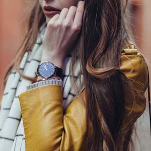 a partial view of a young brunette woman wearing a mustard colored leather jacket, with a white scarf around her neck and a black wrist watch