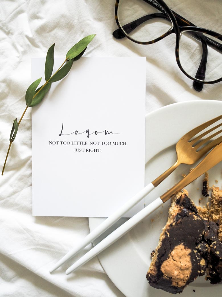 Slow design principles: A stylish flatlay with a card that reads Lagom Not too much, not too little. Just right. Next to it there a slice of cake on a white plate and cutlery.