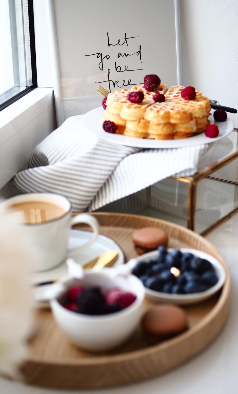A lifestyle image of cakes, and fruits laid out. In the background there is a white board with a sign that reads Let go and be free.