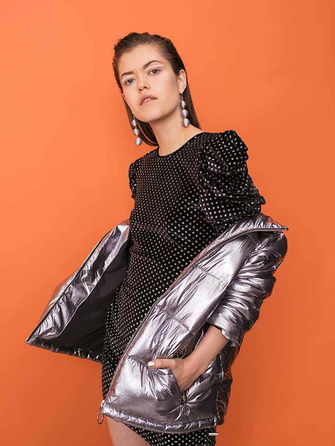 A great black dress with metallic accents and slightly puffed sleeves looks very upbeat when combined with a silver metallic bomber jacket. Image by Miss Selfridge.