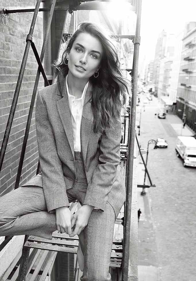 A romantic black and white image of a beautiful woman model sitting on the fire escape stair landing in her stylish gray power suit. Image by nextplc.co.uk.