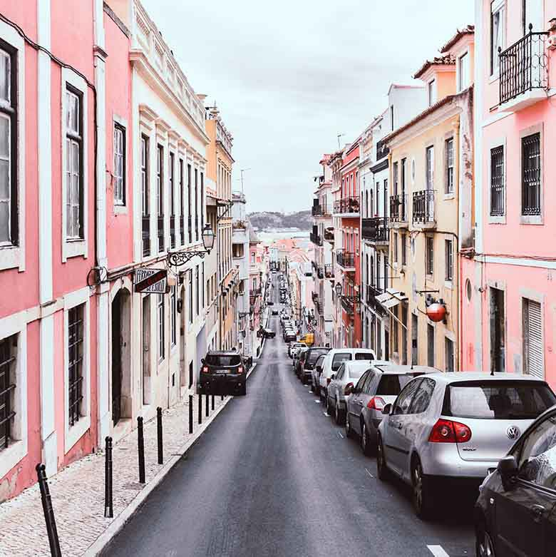 A street going down with pink houses on either side of it.