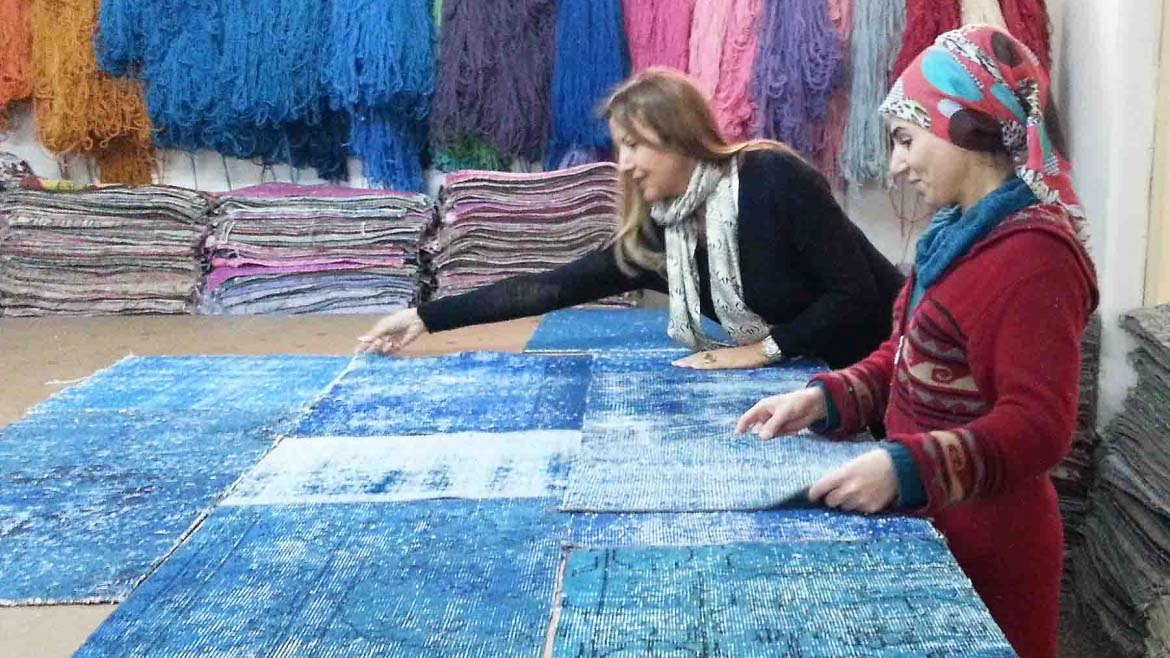 Argyriou and a young woman standing in front of a large table with pieces of patches that will make a rug