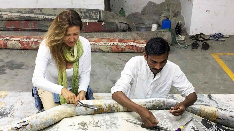 An artisan next to Argyriou cutting up finishing details on a rug