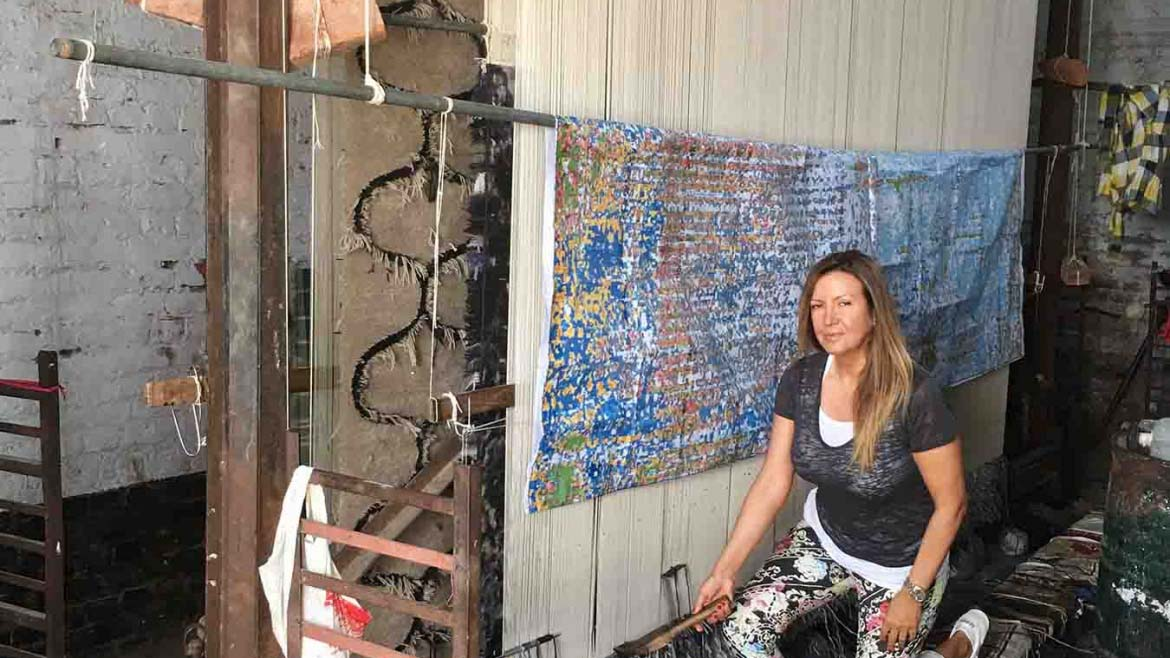 Argyriou standing in front of a vertical loom