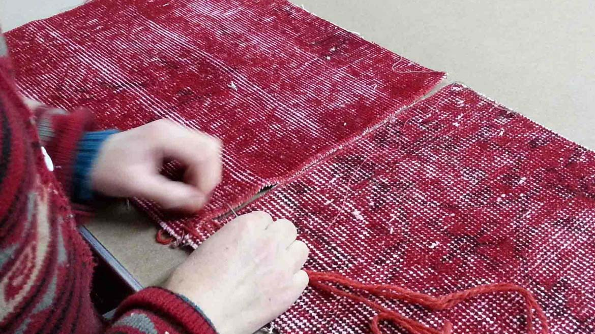 A woman uniting two different patches for a patchwork rung