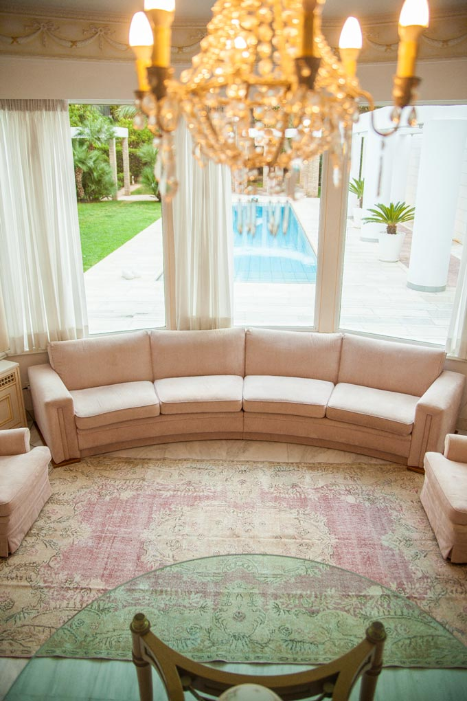 A pinkish vintage area rug looking gorgeous by a bay window nook with a curved blush pink velvet sofa, a chandelier and a garden view of the pool in the background.