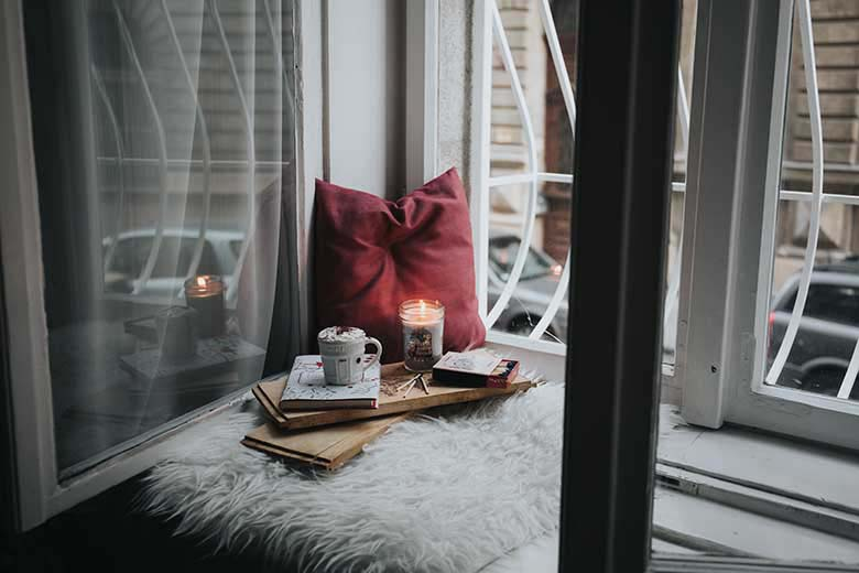 An open window with a nice reading nook arranged using a dark red pillow, a burning candle, and a tray with reading material and a mug