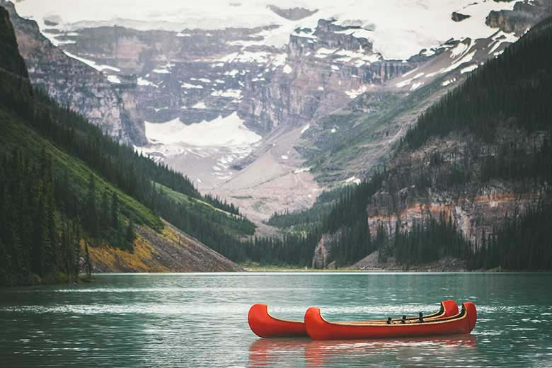 Somewhere in nature, a lake with surrounding white top mountains and two red canoes floating in there