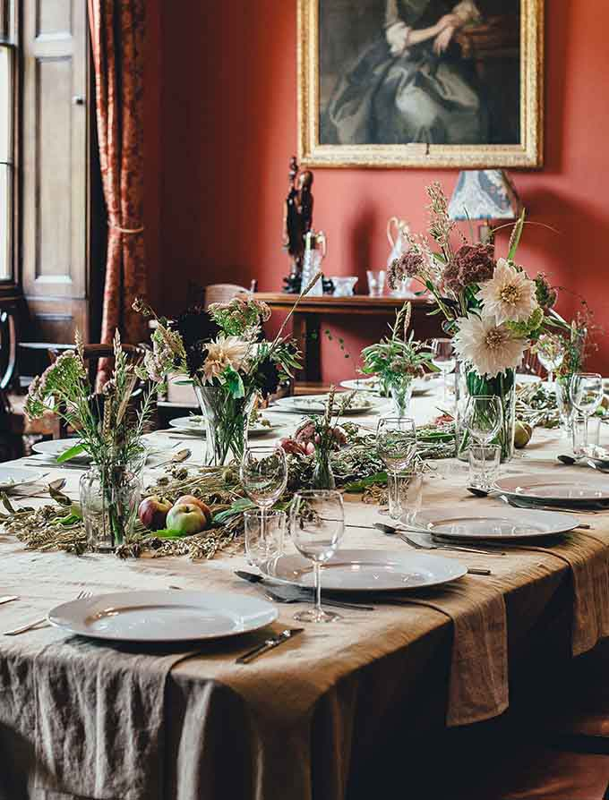 A dining table scape with lots of wild flowers and white china, heavy deep muted red drapes and a muted red accent wall with an oil painting portrait on it.