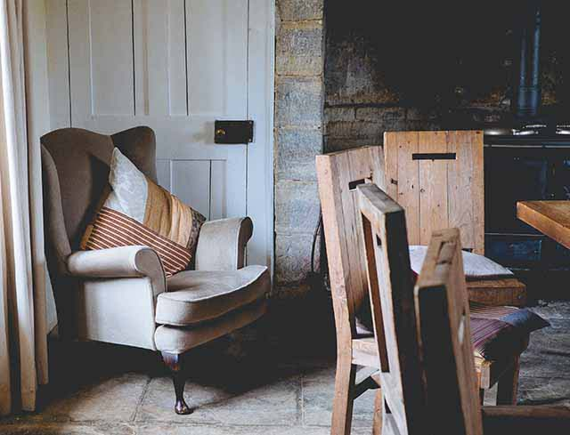 A rustic interior with an armchair and throw pillow on the left and several dining chairs, wooden ones, on the right