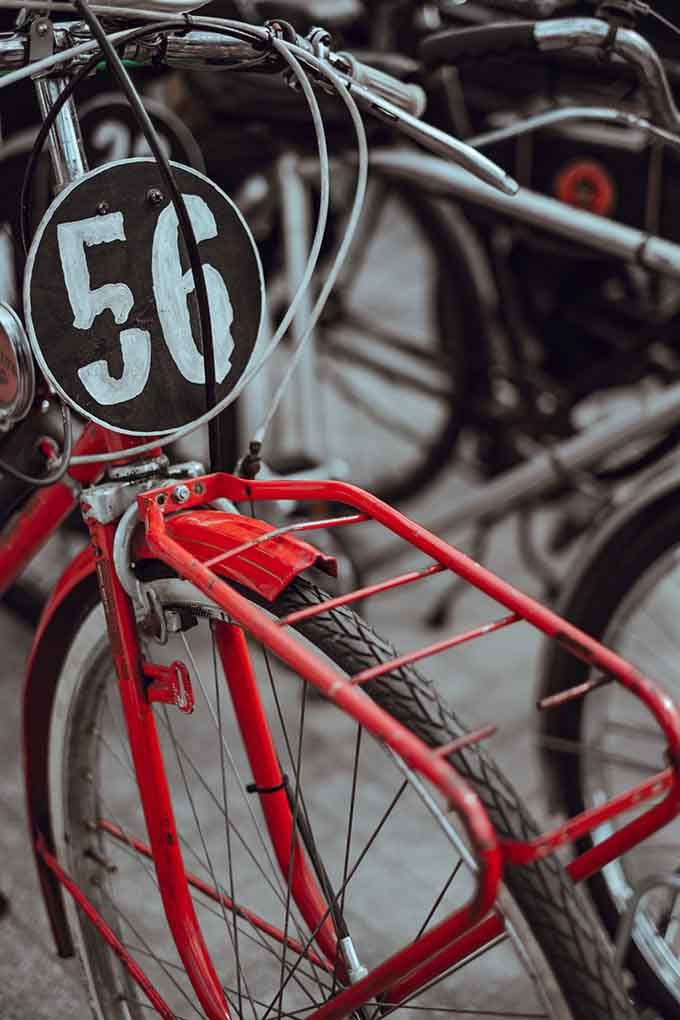 Detail of an old red bicycle with a black badge on it and the number 56 on it