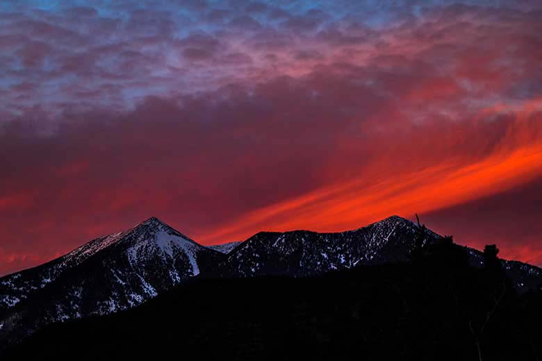 A black mountain ridge in the foreground with a red and purple sky at sunset