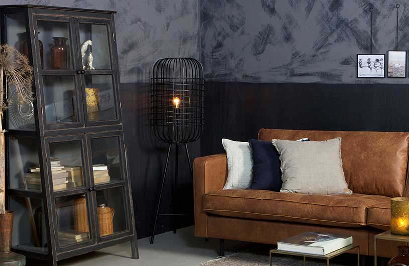 An industrial set with a tanned leather sofa that looks good when combined with this statement black metal hurricane floor lamp besides it. Image by Cuckooland.