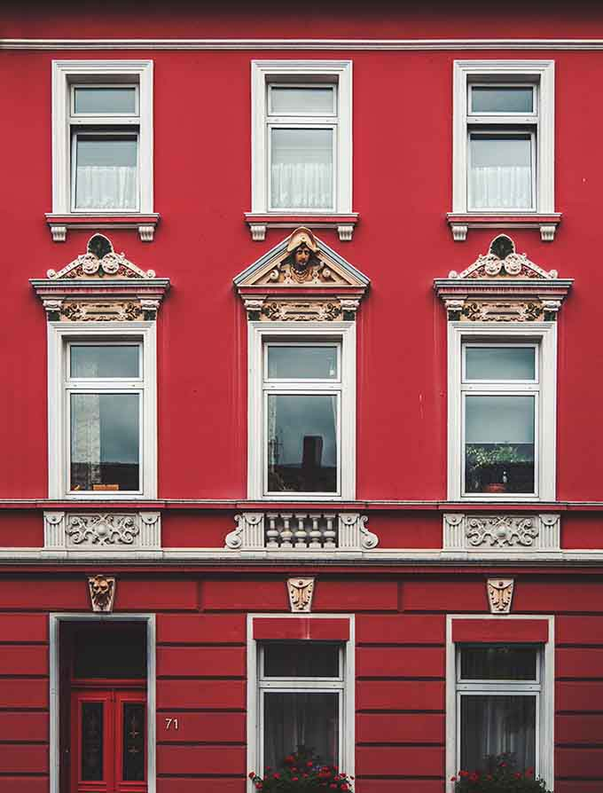An old building with a red facade and white trim frame windows