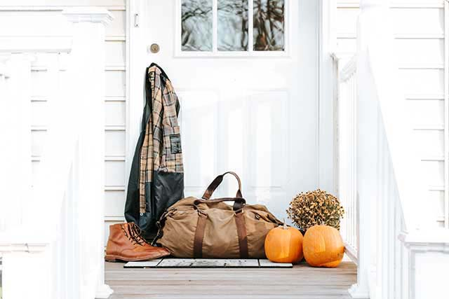 A Burberry jacket hanging from a door's knob with a weekender bag and tanned leather mens shoes next to a bunch of pumpkins in front of a white porch