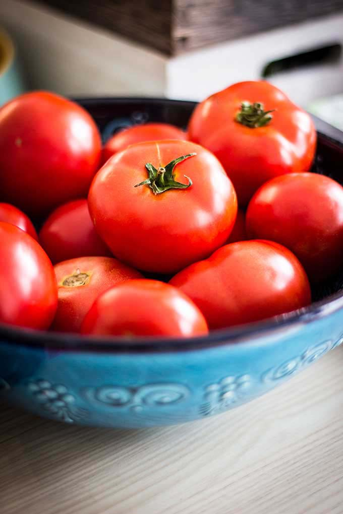 A blue bowl with lots of red tomatoes