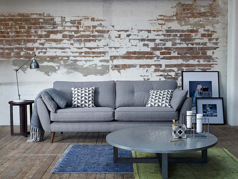 This gray sofa looks perfect against the accent wall with partially exposed brickwork. Image by DFS Furniture.