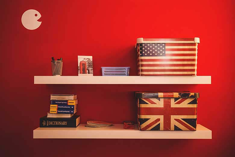 A red wall as a backdrop for two floating shelves with boxes, books and stationary on top of them. The two boxes have the American flag and the British flag on them.