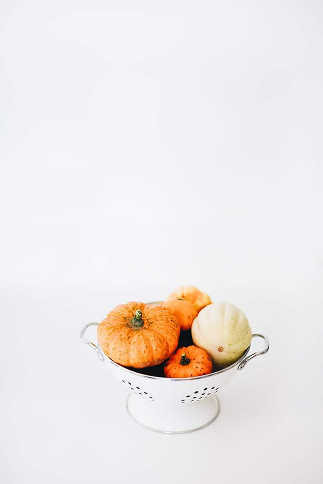 A minimal image of a few orange and a white pumpkins in a white drainer in an all white surrounding