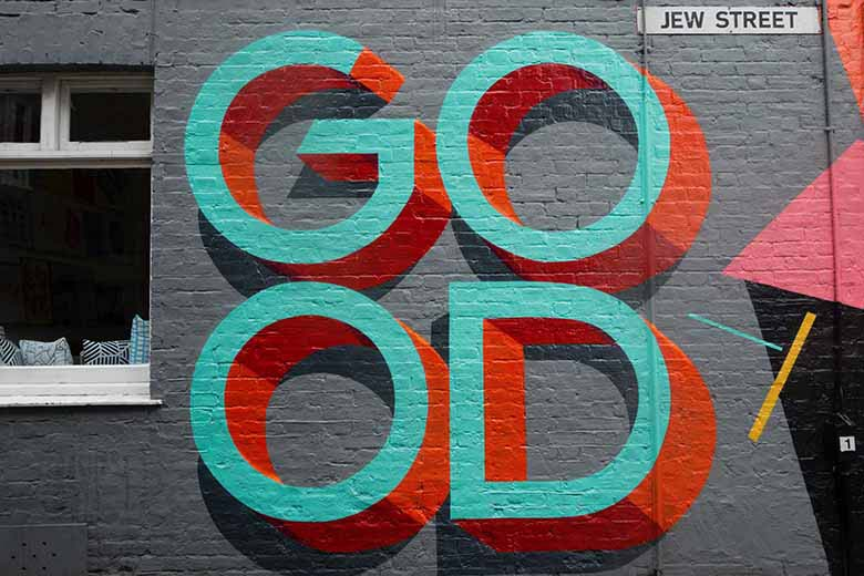 A gray xeterior wall with the word GO-OD written on it with graffiti in 3D teal lettering and red shadows