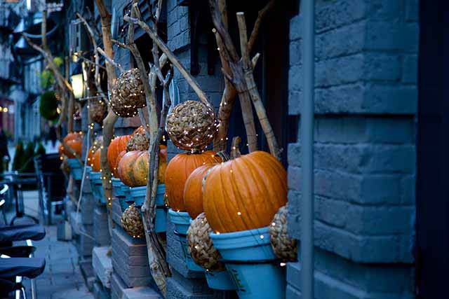 Large orange pumpkins in blue buckets as Halloween decor in the exterior of a blue home. Image taken at an angle.