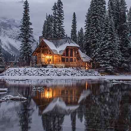 A cabin surrounded by nature in snow nearby a lake