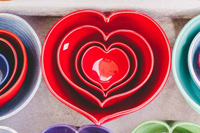 Red heart shaped crockery stacked up inside each other on a table next to more others in various colors