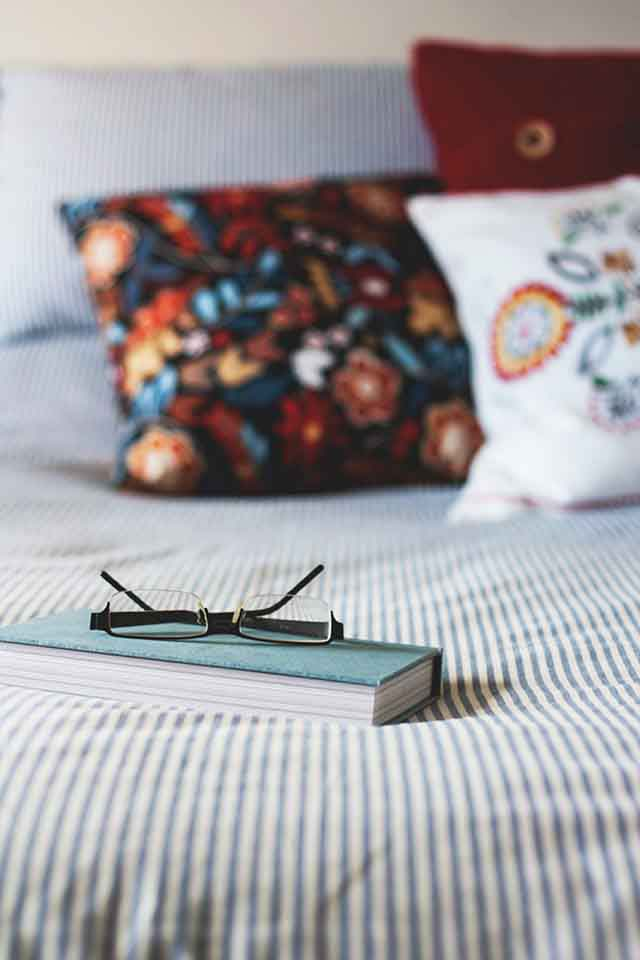 A book and reading glasses on a striped bedding in the foreground. Two different colorful throw pillows on the bed in the background