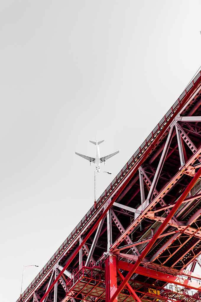 Detail from below, of a red steel bridge while a white airplane is flying overby
