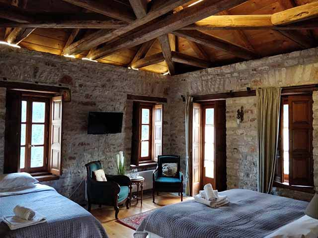A rustic interior of a cabin bedroom. The walls are made of stone and the pitched roof out of timber