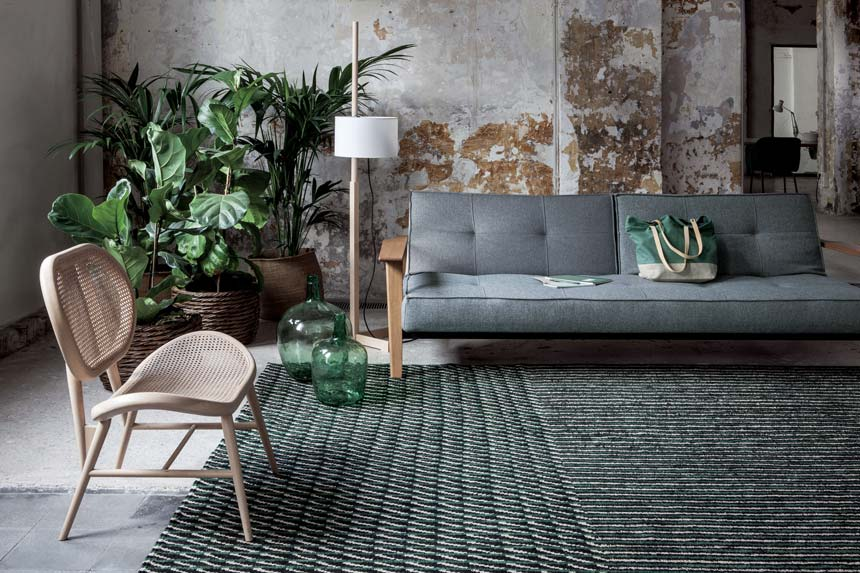 A green textured area rug in a living room with an organic vibe. Image via Nest.co.uk.