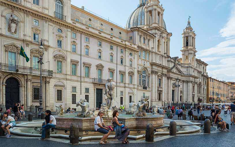 Palazzo Pamphili in Piazza Navona in Rome with a fountain in front of it and lots of passerbys