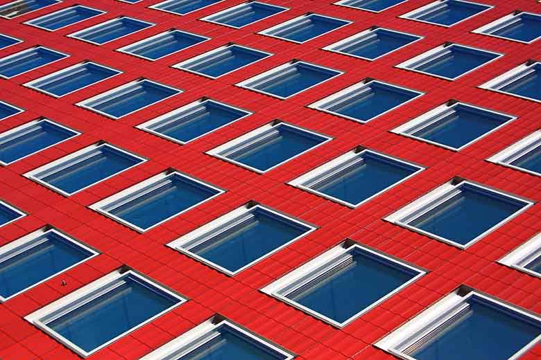 A red facade of a building pictured sideways thus the windows look blueish