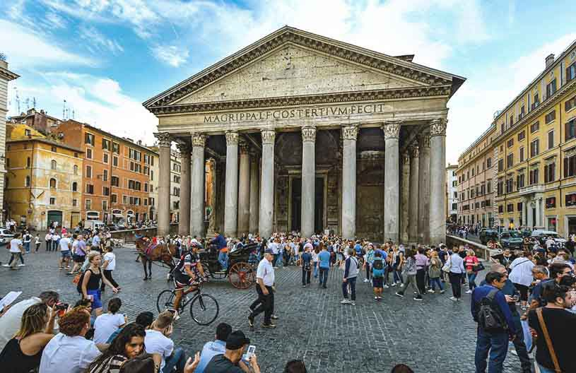 View of the exterior of the Pantheon in Rome with lots of passerbys