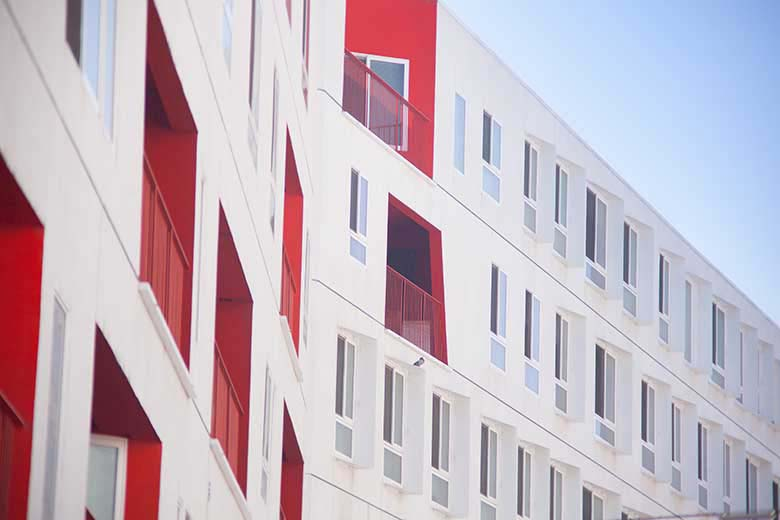 Exterior white facade of a building with some red details on a few walls and window inserts