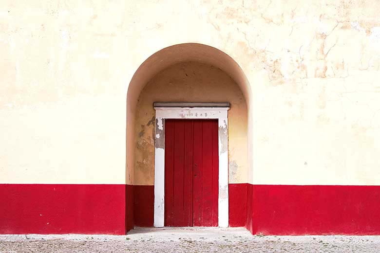 A red exterior door in an arched wall insert with a band of red color running across the exteriors walls about a meter high while the rest of the height wall is an off-beige color