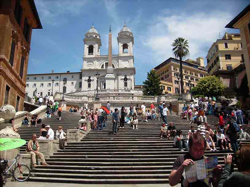View of the Spanish steps in Rome with the church atop and lots of tourists about