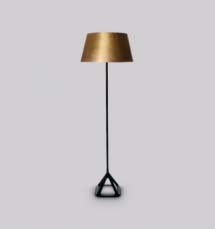 A floor lamp with a brass lamp shade and a black stand designed by Tom Dixon