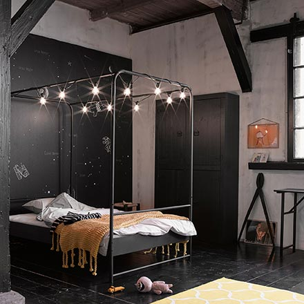 An industrial space with exposed dark wood beams has been styled as an industrial bedroom that has a canopy of Edison bulb lights. Image by Cuckooland.