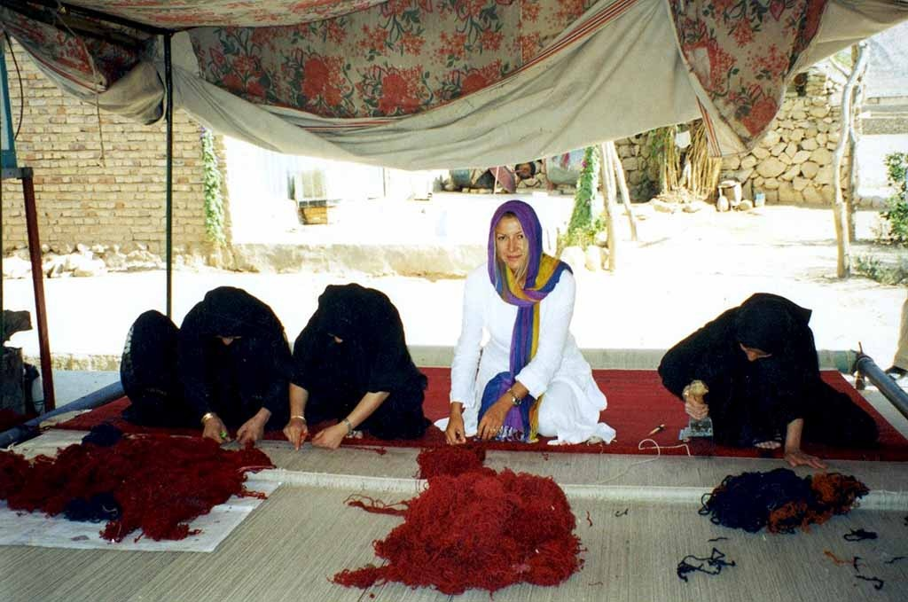 Argyriou in between three other Iranian women who are weaving a rug over a horizontal loom.