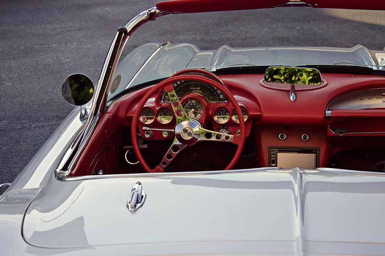 A white convertible car with a red leather dashboard and steering wheel