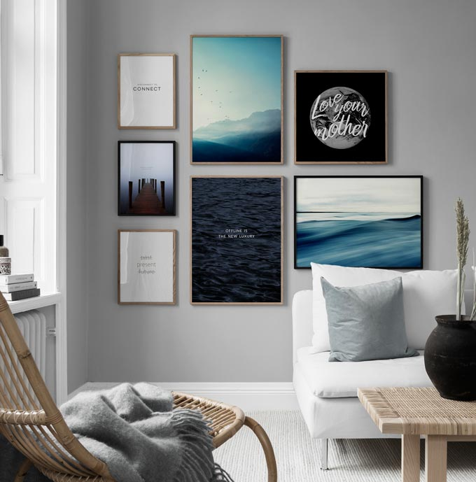 A nature inspired theme gallery wall creates a serene focal point in a bright minimal living room. Image by Desenio.