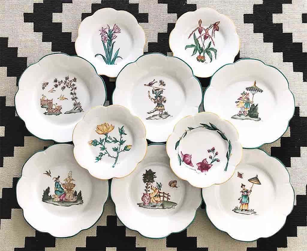 An assortment of various plates with hand painted depictions on them of flowers and of Chinese figures