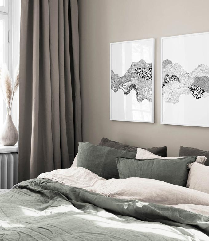 Two art prints in one grouping hanging over a muted grey contemporary bedroom. Image by Desenio.