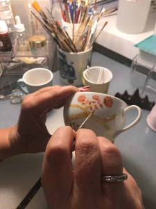 A close up on Marta's hands while painting a coffee cup