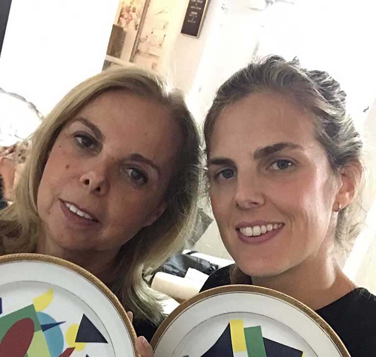 Marta and her daughter, each holding up a dinner plate
